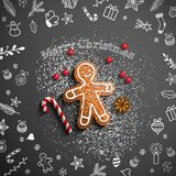 Gingerbread man with chalk doodles on black background. Christmas theme, gingerbread man lying on blackboard with chalk doodles, candy cane, sugar and some stock illustration