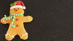 Gingerbread man with red Santa hat green and white scarf on a black background with writing space stock photography