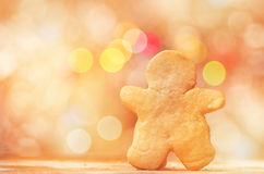 Gingerbread man cookie on red and yellow holiday bokeh. Abstract Christmas background. Royalty Free Stock Image
