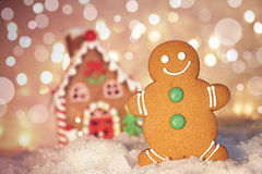 Gingerbread man cookie standing beside house Stock Image