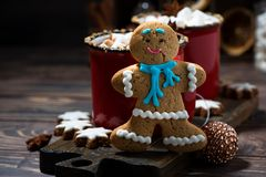Gingerbread man cookies and hot chocolate on wooden background. Closeup royalty free stock photography