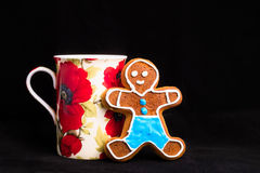 Gingerbread man and cup of tea on black velvet Stock Image