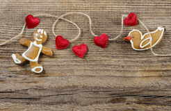 Gingerbread man and cute red hearts. On wooden background. Copy space Royalty Free Stock Photo