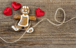 Gingerbread man and cute red hearts. On wooden background. Copy space Stock Photo