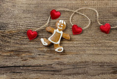 Gingerbread man and cute red hearts. On wooden background. Copy space Royalty Free Stock Images