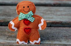 Gingerbread Man. Felt ginger bread man on shabby chic, weathered wooden bench background , traditional shabby chic christmas Stock Photography