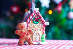 Gingerbread man in front of his candy ginger house. Background the Christmas tree lights. See my other works in portfolio royalty free stock image