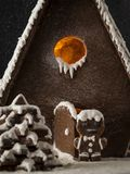 Gingerbread man in front of gingerbread house Snowing Close up stock photo