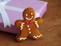 Gingerbread man in front of wrapped gift Royalty Free Stock Photos