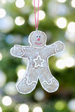 Gingerbread Man Hanging Against Christmas Lights. Closeup of gingerbread man hanging against Christmas lights stock photography
