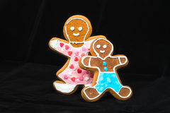 Gingerbread man, mother and son on black velvet Royalty Free Stock Images