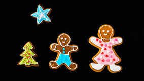 Gingerbread man, mother son fir tree and star on black velvet Royalty Free Stock Image