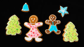 Gingerbread man, mother son and fir trees on black velvet Royalty Free Stock Images