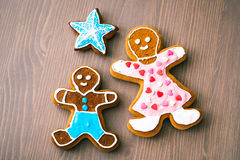 Gingerbread man, mother and son on wooden table Stock Photos