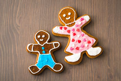 Gingerbread man, mother and son on wooden table Royalty Free Stock Photography