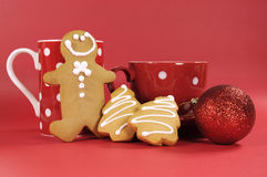 Gingerbread man with red polka dot coffee mug and tea cup with Christmas tree shape cookies. Against a red background Stock Photo