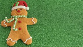 Gingerbread man with red Santa hat green and white scarf on a green background with writing space stock photography