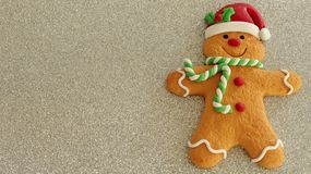 Gingerbread man with red Santa hat green and white scarf on a silver background with writing space royalty free stock photography
