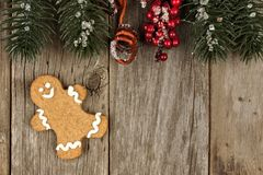 Gingerbread man on rustic wood with tree branch border Stock Photos
