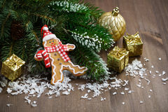 Gingerbread man in the snow, fir branches and decorations Stock Image