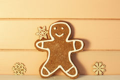 Gingerbread man with snowflakes on wooden background Stock Image