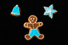Gingerbread man with star and bell on black velvet Royalty Free Stock Photography