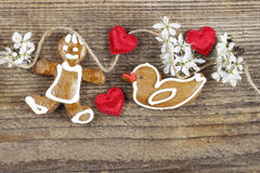 Gingerbread man, sweet duck and cute red hearts. On wooden background. Copy space Stock Photos
