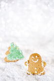 Gingerbread man and tree on a festive Christmas snow background Royalty Free Stock Photos