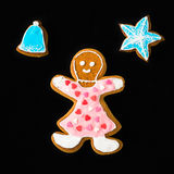 Gingerbread man, woman, with star and bell on black velvet Stock Photos