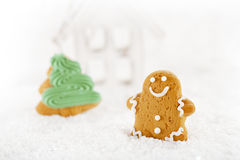 Gingerbread man and wooden house on a festive Christmas snow Royalty Free Stock Photo
