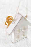 Gingerbread man and wooden house on a festive Christmas snow Stock Photo
