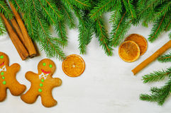Gingerbread mans and Christmas tree branches on wooden backgroun Royalty Free Stock Image