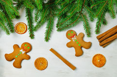 Gingerbread mans and Christmas tree branches on wooden backgroun Stock Photography