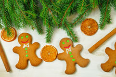 Gingerbread mans and Christmas tree branches on wooden backgroun Royalty Free Stock Photo