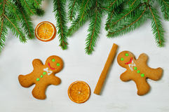 Gingerbread mans and Christmas tree branches on wooden backgroun Royalty Free Stock Images