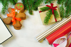 Gingerbread mans, gift box and Christmas tree branches on wooden Royalty Free Stock Photography