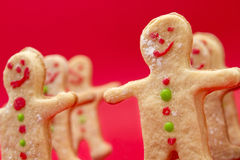 Gingerbread Men Cookies. Gingerbread christmas cookies stood up and shot at an angle over fuschia paper Royalty Free Stock Photos