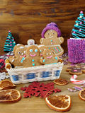 Gingerbread men cookies in a wicker basket surrounded by Christmas decorations. On a wooden background Stock Photos