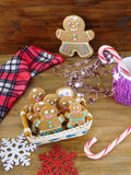 Gingerbread men cookies in a wicker basket surrounded by Christmas decorations. On a wooden background Stock Image