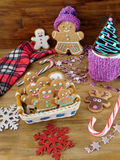 Gingerbread men cookies in a wicker basket surrounded by Christmas decorations. On a wooden background Royalty Free Stock Photos