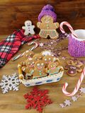 Gingerbread men cookies in a wicker basket surrounded by Christmas decorations. On a wooden background Royalty Free Stock Images