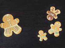 Gingerbread men and deers are framing empty place for a text. Dark Christmas background. Gingerbread men and deers are framing empty place for a text stock image