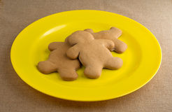 Gingerbread men on a large yellow plate Stock Image