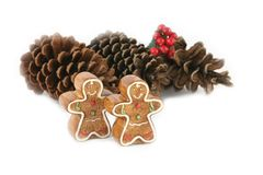 Gingerbread men and pine cones (focus on gingerbread men) stock images