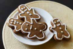 Gingerbread men on a white plate on black background Royalty Free Stock Images