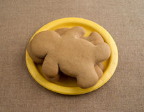 Gingerbread men on a yellow paper plate. Three freshly baked gingerbread men on a small paper yellow plate atop a wrinkled burlap tablecloth illuminated with Stock Images