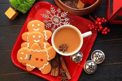 Above photo of three gingerbread men and coffee with star anise. Wooden background with red plate with tree gingerbread men a mug of coffee. Inside the coffee stock image