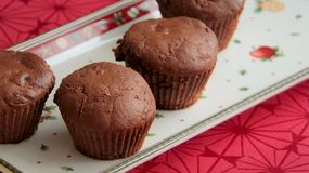 Gingerbread muffins with dark cocoa and plum butter served on Christmas plate. Chocolate muffins with gingerbread spices, dark cocoa and pumpkin served on Stock Photos