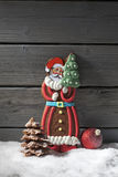 Gingerbread santa claus christmas bulb chocolate christmas tree on heap of snow against wooden background Royalty Free Stock Image