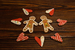 Gingerbread in the shape of hearts and figurines of people. Two handmade cookie in the shape of men and heart in the middle between them on the rough wooden Stock Images